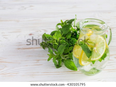 Homemade lemonade with fresh lemon and mint on white wooden background. Fresh water, refreshment drink - stock photo