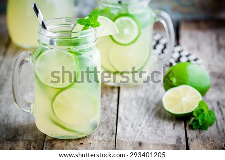homemade lemonade with lime, mint in a mason jar on a wooden rustic table - stock photo