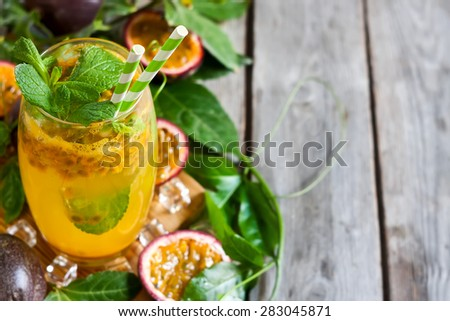 Homemade lemonade with passionfruit, mint leaves and ice cubes on old wooden background. Copy space background. - stock photo