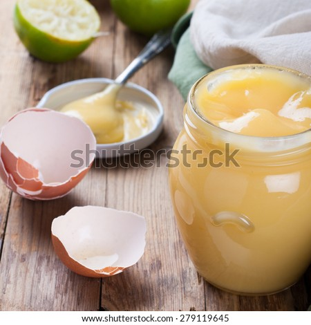 Homemade lime curd in glass jar with fresh limes and egg shells on old wooden background. Selective focus - stock photo