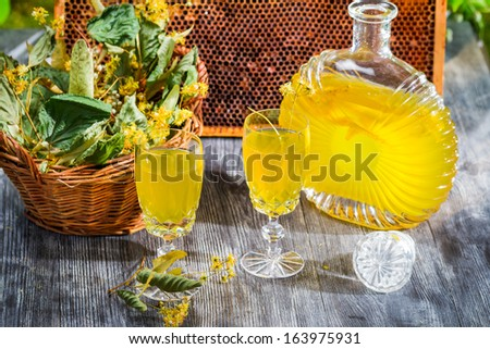 Homemade liqueur made of honey and dry lime leaves - stock photo