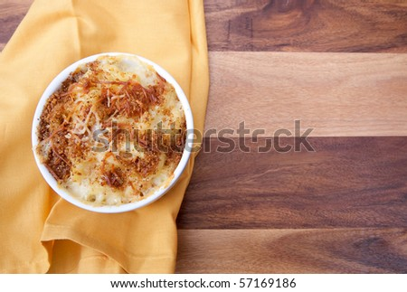 homemade macaroni and cheese in a ramekin with copyspace on a yellow napkin and wood surface - stock photo