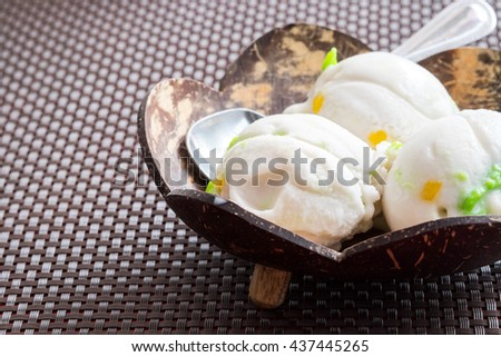 Homemade mango ice cream on wood bowl, served over wooden textured background. Top view, close up - stock photo