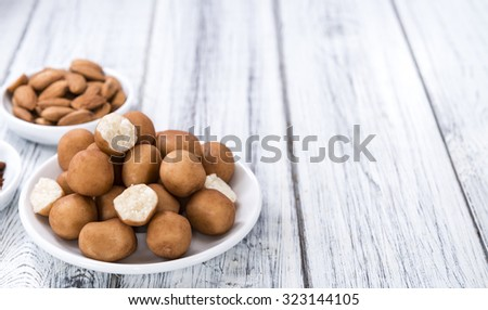 Homemade Marzipan Potatoes (German cuisine) on rustic wooden background - stock photo
