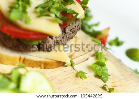 Homemade meat and cheese sandwich preparation on a wooden board