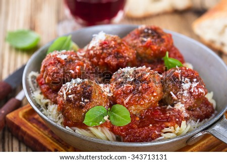 Homemade meatball made with ground beef and marinara sauce with Italian pasta in  frying pan  on rustic wooden table, top view - stock photo