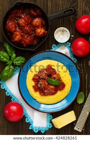 Homemade meatballs in tomato sauce with polenta as a garnish. - stock photo