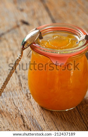 Homemade melon jam in a preserving jar with a spoon on old wooden table - stock photo
