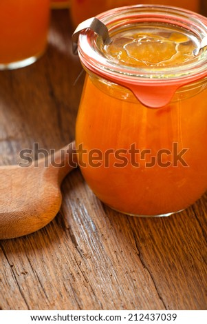 Homemade melon jam in a preserving jar with a wooden spoon on old wooden table - stock photo