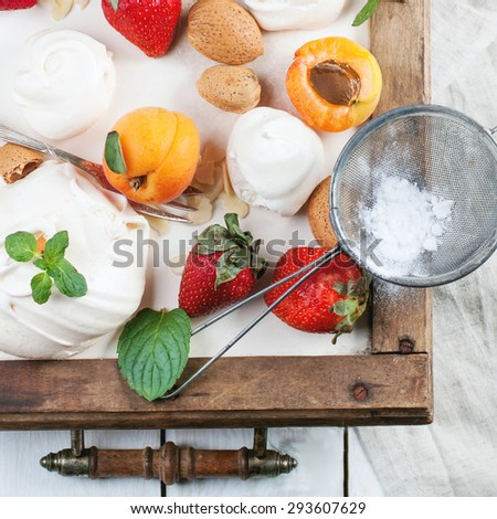 Homemade meringue with apricots, strawberries, almonds and cream. Ingredients for dessert Eton mess. Top view. Square image. - stock photo