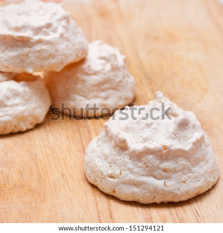 homemade meringues on a wooden chopping board
