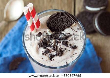 Homemade milkshake (chocolate smoothie) with cookies on rustic wooden table close up - stock photo