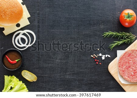 Homemade minced beef, sesame bun, onion, tomato, lettuce, BBQ sauce. Hamburger ingredients on a black background. Space for text. - stock photo