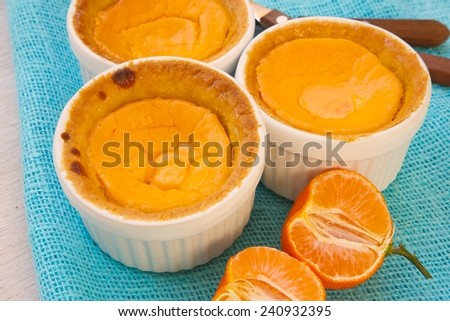 Homemade mini cheese cakes with tangerines in white ceramic moulds. Pieces of tangerines and dessert spoons on a cyan sackcloth - stock photo