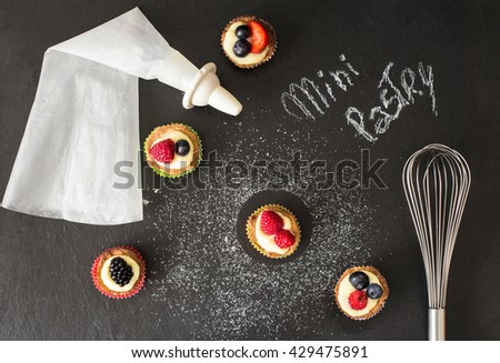 homemade mini pastry with red fruits,  over slate with fine sugar