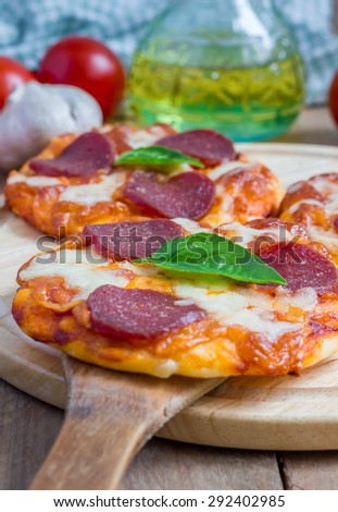 Homemade mini pepperoni pizza on a wooden board