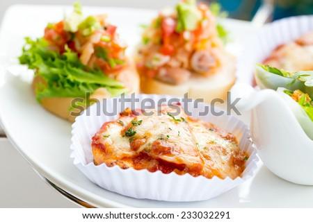 Homemade Mini pizza with chorizo salami sausage and mozzarella cheese - stock photo