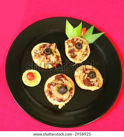 Homemade mini pizzas with sardines and black olives - stock photo