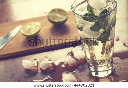 Homemade mojito cocktail, alcoholic or non-alcoholic cocktail on an old brown wooden background, closeup