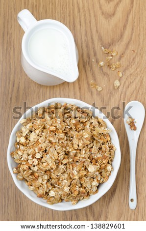 homemade muesli and a jug of milk for breakfast on a wooden table, top view vertical - stock photo