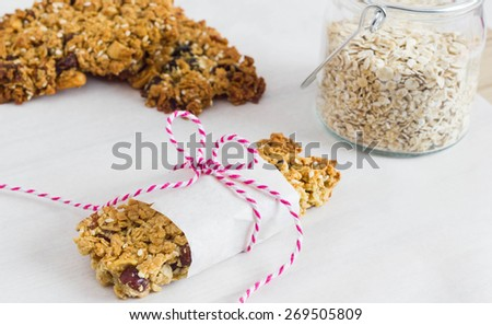 Homemade muesli bars with natural ingredients on a white background, wrapped in white paper with pink cord. - stock photo