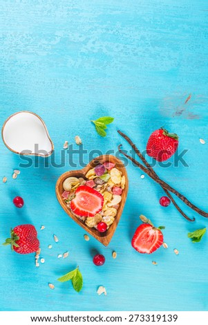 Homemade muesli with nuts, candied fruits and berries in a heart-shaped wooden bowl on a blue table, selective focus - stock photo