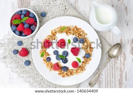 homemade muesli with yogurt, raspberries and blueberries top view, horizontal - stock photo