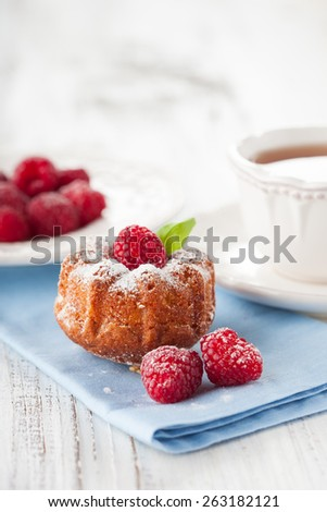 Homemade muffin with a fresh raspberries and cup of tea on white wooden background, selective focus - stock photo