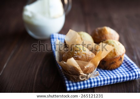 Homemade muffins in blue napkin and jug of milk on old wood table. Still life - stock photo