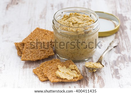 homemade mustard in a glass jar and crackers, horizontal - stock photo