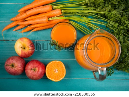 Homemade natural carrot juice in glass on rustic blue wooden table in background - stock photo