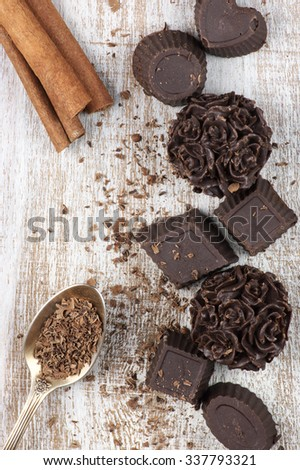 Homemade natural chocolate candies with ingredients on rustic wooden background. - stock photo