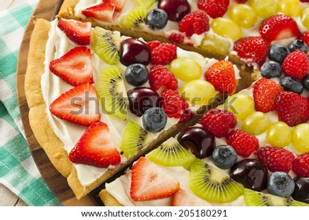 Homemade Natural Fruit Pizza with Frosting and Berries - stock photo