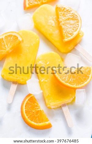Homemade, natural orange ,refreshing summer popsicle. From above flat lay on white marble with fresh orange slices. - stock photo