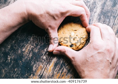 Homemade oat and nut cookies in hands on wood table