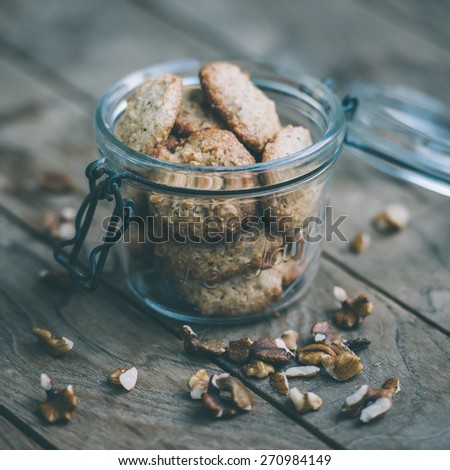 Homemade oat and nut cookies on wooden table. Toned picture - stock photo