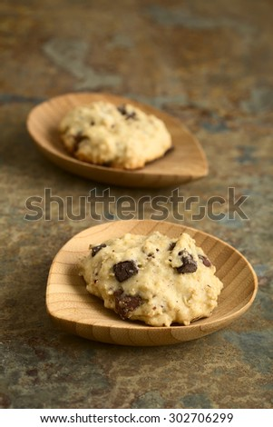 Homemade oatmeal and chocolate cookie on small bamboo plates, photographed with natural light (Selective Focus, Focus on the front of the first cookie) - stock photo