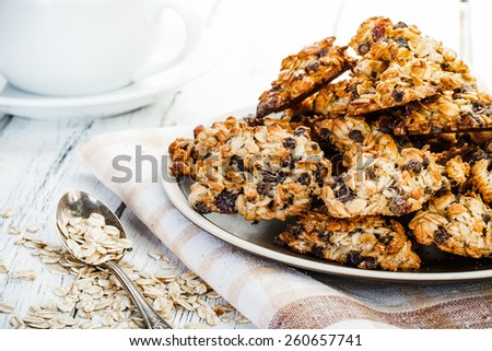 homemade oatmeal cookies, cup of coffee, spoon with oat and old textile tablecloth on old white wooden table - stock photo