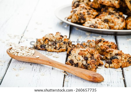 homemade oatmeal cookies on plate and spoon with oat on old white wooden table - stock photo