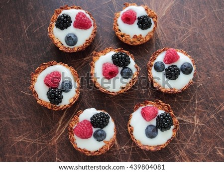 Homemade oatmeal tarts with light yogurt and fresh blackberries, raspberries and bilberries