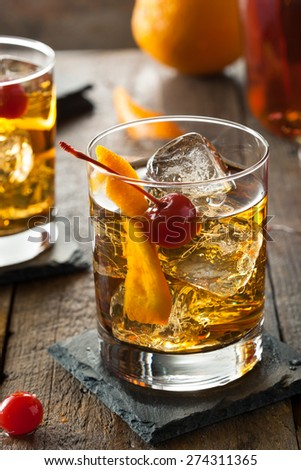 Homemade Old Fashioned Cocktail with Cherries and Orange Peel - stock photo
