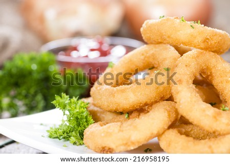 Homemade Onion Rings with fresh herbs on rustic wooden background - stock photo