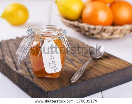 Homemade orange jam in glass jar on  wooden background. Selective focus.
