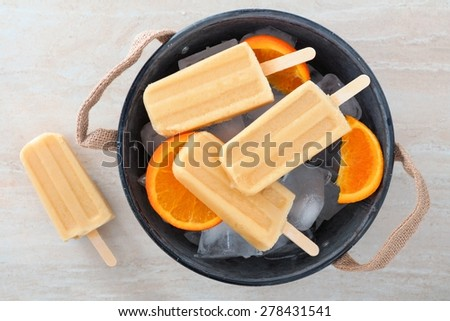 Homemade orange yogurt popsicles in a rustic ice filled tin pail with fresh fruit slices - stock photo