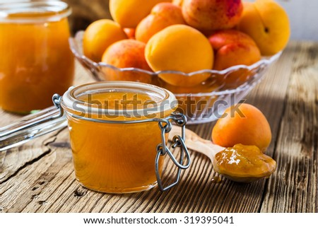 Homemade organic apricot jam in glass jar and ripe apricots on  wooden rustic table - stock photo