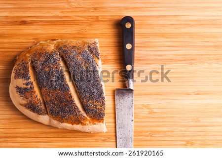 Homemade Organic Bread loaf lying on a wood Board, sliced with the knife, ready for making a sandwich,  - stock photo