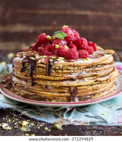 Homemade Pancake cake with dark chocolate sauce, fresh raspberry, pistachios nuts and mint on a dessert plate, selective focus - stock photo