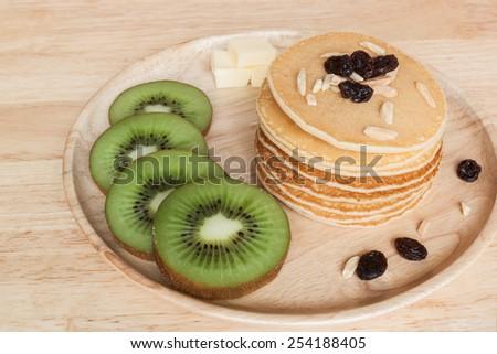 homemade pancake with kiwi raisins almond and butter on wood plate - stock photo