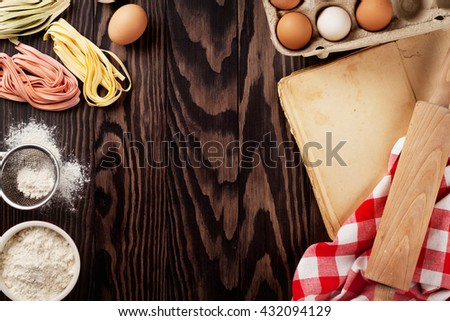 Homemade pasta cooking, utensils and vintage cooking book on wooden table. Top view with copy space - stock photo