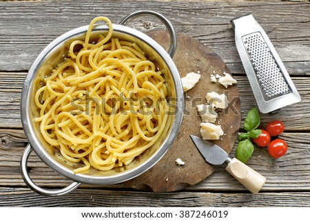 Homemade pasta in colander with grater, tomato, basil  on wooden background  - stock photo